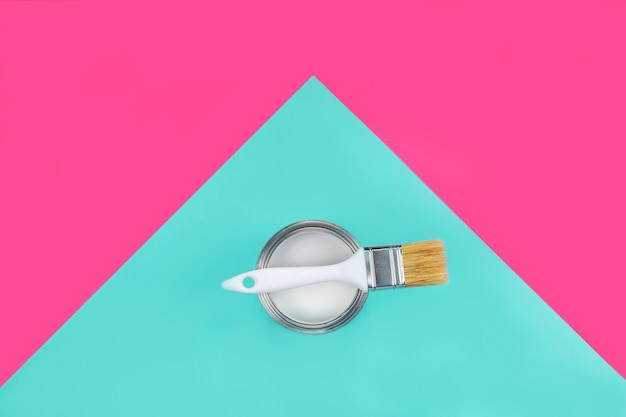 Can of paint with brush on them on pink and blue Premium Photo