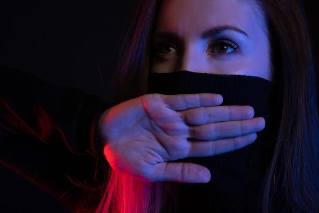 何も言えない。女の子はネオンの交差した手のひらで彼女の口を閉じます。 Premium写真