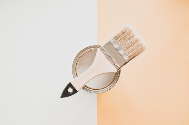 Can of white paint with a brush, on a bright background. Premium Photo