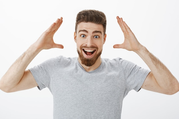 Can you imagine i got job. charismatic joyful and excited handsome male model with beard in grey t-shirt raising hands near head smiling broadly receiving good news and retelling it friends happily Free Photo