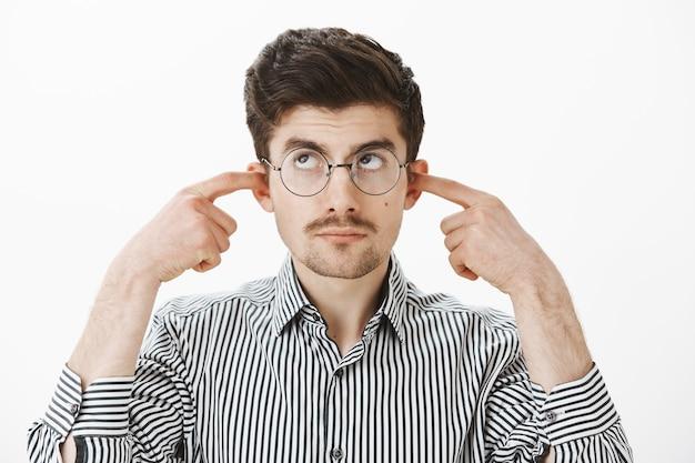 Puoi spegnere la musica per favore, sto studiando. calma dispiaciuto nerd studente maschio in occhiali da nerd e maglietta a righe, che copre le orecchie con le dita indice, guardando in alto, essendo disturbato dal forte rumore Foto Gratuite