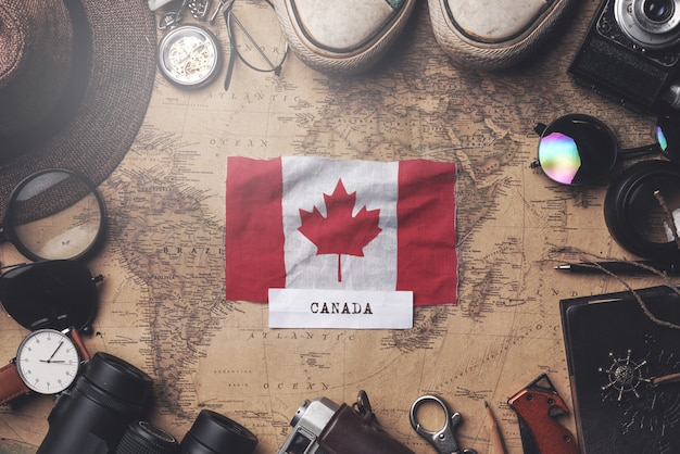 Canada flag between traveler's accessories on old vintage map. overhead shot Premium Photo
