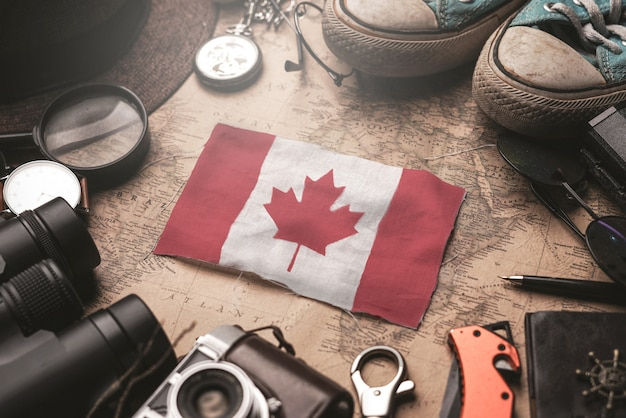 Canada flag between traveler's accessories on old vintage map. tourist destination concept. Premium Photo