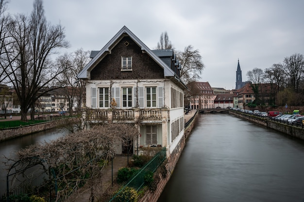 Canal surrounded by buildings and greenery under a cloudy sky in strasbourg in france Free Photo