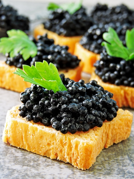 Canapes with black caviar. Premium Photo