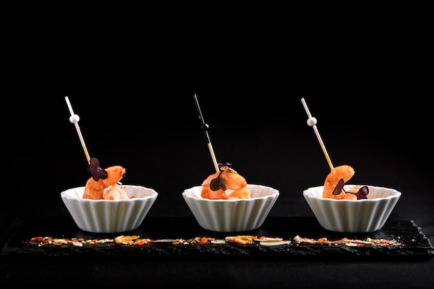 Canapes with tiger prawns on a skewer. the concept of catering food. Premium Photo
