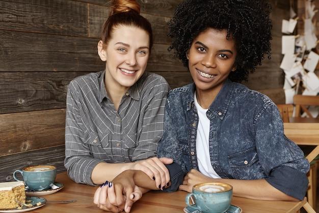 手を繋いでいると幸せな笑顔でカメラ目線のかわいい同性愛カップルの率直な屋内撮影 無料写真