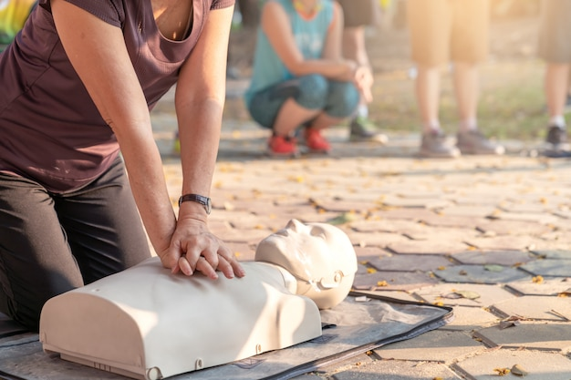 Candid of mature asian female or older runner woman training on cpr demonstrating class in outdoor park and put hands over cpr doll on chest. first aid training for heart attack people or lifesaver. Premium Photo