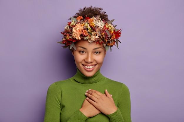 Il colpo schietto di una donna sorridente attraente si sente grata, ouches al petto con gratitudine, indossa una ghirlanda autunnale, posa al coperto in abbigliamento casual Foto Gratuite