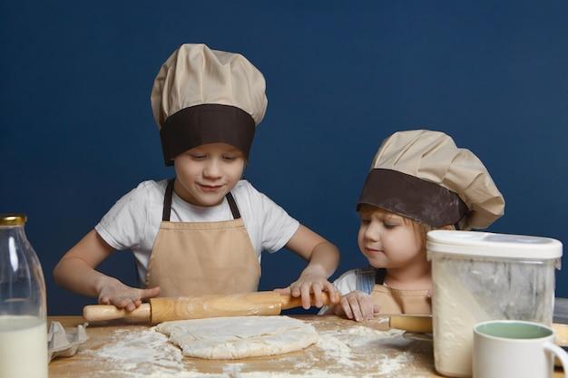 Candido colpo di affascinante bambina in cappello da cuoco guardando il suo fratello anziano che impasta pasta per biscotti o torta Foto Gratuite