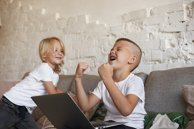 Candid shot of emotional ecstatic teenage boy with braces sitting on couch with his little brother, using laptop computer, shouting and pumping fists, rejoicing at his winning in video game Free Photo