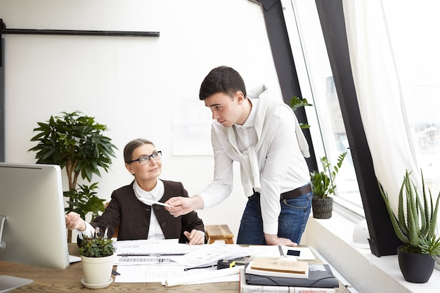 Candid shot of happy middle aged woman architect working in office with young male colleague who is sharing creative ideas and fresh vision on constuction project, pointing finger at computer screen Free Photo
