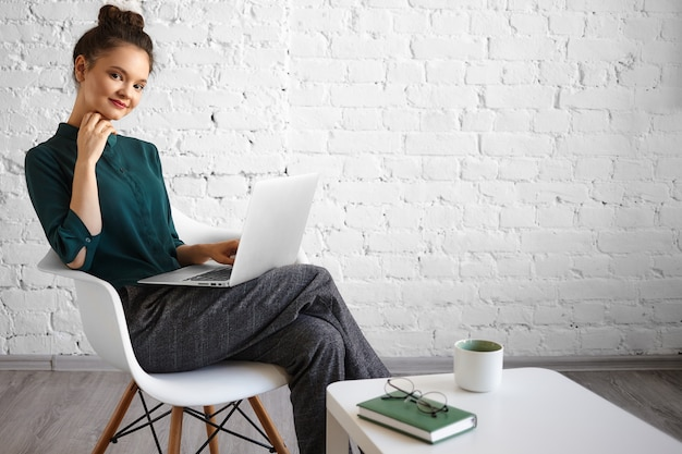 Candid shot of joyful beautiful young caucasian female freelancer using generic laptop for distant work, sitting casually in chair at coffee table with mug, book and eyeglasses. people and technology Free Photo