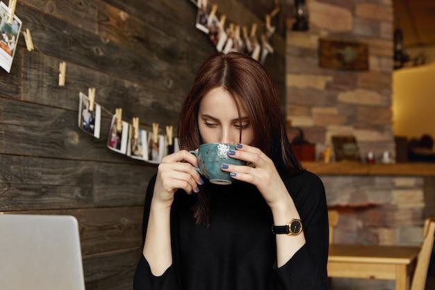 開いているラップトップコンピューターの前に座って、カフェでリモートで作業しながら小さな休憩中に大きなカップからコーヒーやお茶を飲んで黒い服を着た美しいブルネットの女性フリーランサーの率直なショット 無料写真