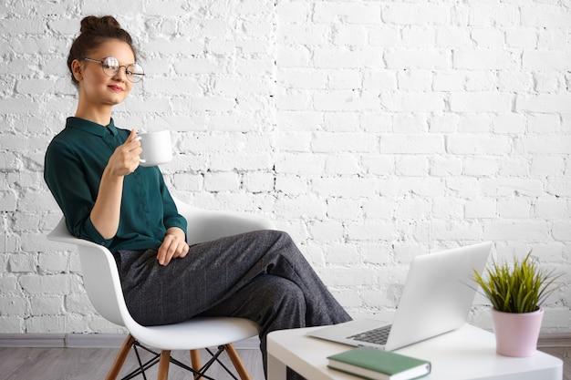 Откровенный снимок модной молодой женщины-фрилансера в круглых очках и пучка волос, наслаждающейся кофе или чаем в коворкинге, сидя в кресле перед открытым портативным компьютером и улыбаясь Бесплатные Фотографии