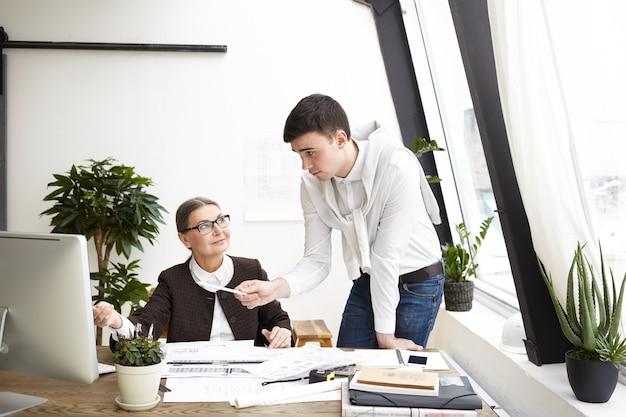 コンピューター画面に人差し指で、建設プロジェクトで創造的なアイデアと新鮮なビジョンを共有している若い男性の同僚とオフィスで働いている幸せな中年女性建築家の率直なショット 無料写真