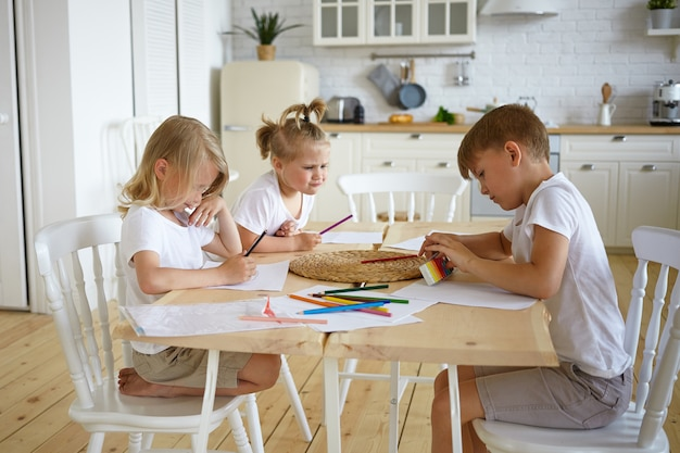 Откровенный снимок трех очаровательных детей-братьев и сестер европейской внешности, которые сидят за кухонным столом и вместе рисуют семейный снимок красочными карандашами, сосредоточив серьезные выражения. Бесплатные Фотографии