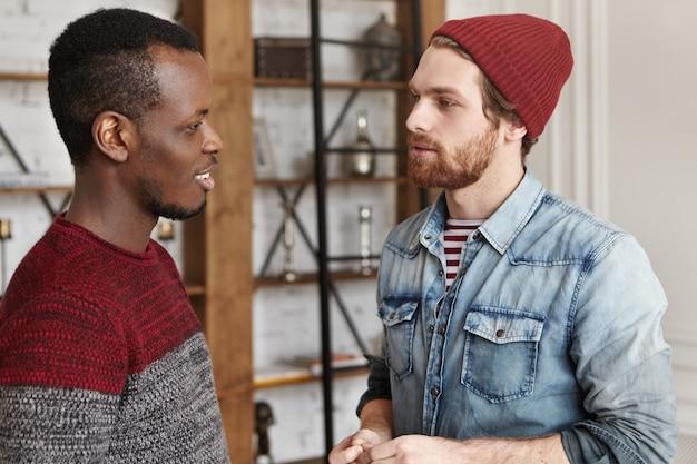 互いに向かい合って立っているさまざまな人種の2人のスタイリッシュな男性の親友の率直なショット 無料写真