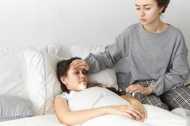 寝室に座って、病気の娘の額に手を握って、心配して動揺している若い女性の率直なショット、 無料写真