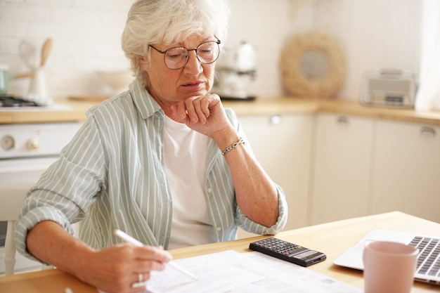 Candid shot of serious caucasian retired woman in spectacles calculating expenses, trying to save money for expensive purchase, paying domestic bills online using electronic gadget at kitchen table Free Photo