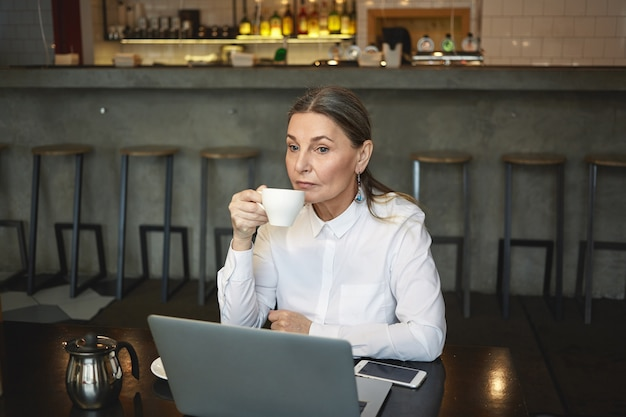 Candid colpo di premurosa imprenditrice matura in camicia formale gustando un caffè durante il pranzo, seduto al bar con laptop generico e telefono cellulare con schermo vuoto sul tavolo. affari, età e tecnologia Foto Gratuite