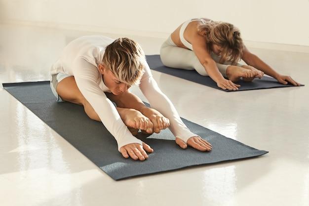Colpo schietto di giovani europei maschi e femmine che praticano yoga al chiuso, stretching, seduti su stuoie e mettendo le mani sul pavimento. due yogi attivi sani che si esercitano nello sport club, facendo piegamento in avanti Foto Gratuite