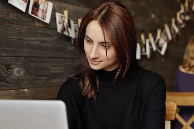 Candid view of attractive brunette female translator in black dress using wifi at cafe Free Photo