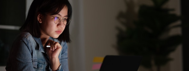 Candid of young attractive asian female student sitting on desk with smart digital gadget looking at notebook working at late night with project research, graphic designer or programmer concept. Premium Photo