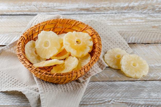 木製とキッチンタオルの表面にバスケットに砂糖漬けのパイナップル 無料写真