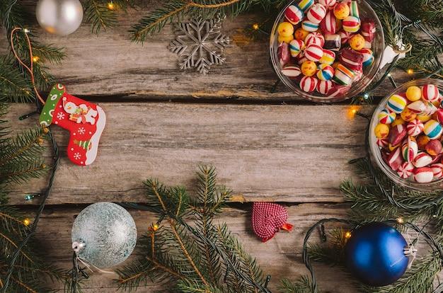 Caramelle, palline di natale e rami di abete rosso su una superficie di legno Foto Gratuite
