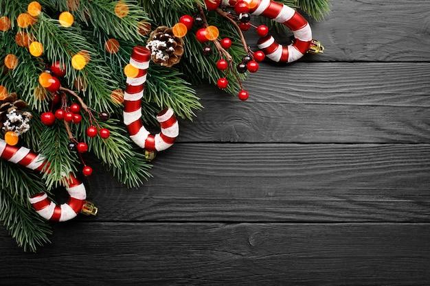 キャンディー、モミの枝、コーン、そして黒い木の表面に赤い果実 Premium写真