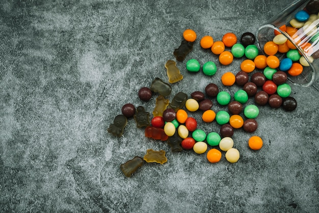 Candies and marmalade scattered on table Free Photo
