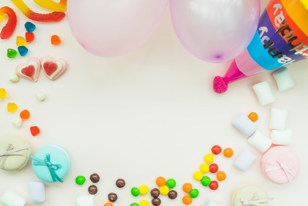Candies; marshmallow; balloons and birthday hat on white background Free Photo
