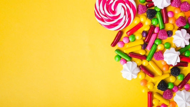 Candies and marshmallows on yellow background Free Photo