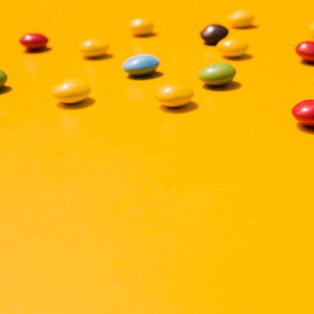 Candies with copy space for writing the text on yellow backdrop Free Photo