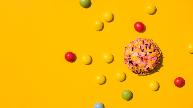 Candies with sprinkle donut on yellow background Free Photo