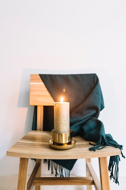 Candle in candlestick on wooden chair Free Photo