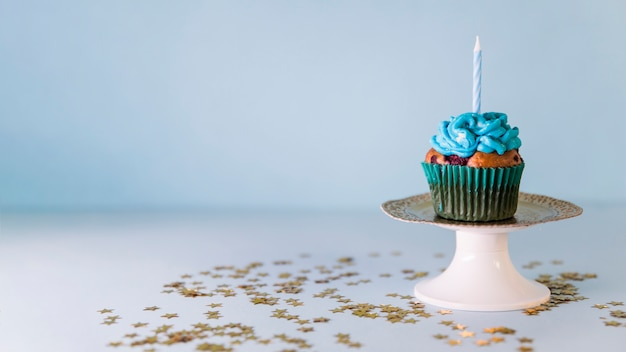 Candle on cupcake over the cakestand against blue background Free Photo