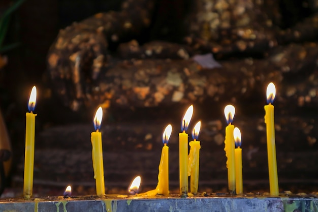 Candle and flame in buddist temple gold buddha background Premium Photo