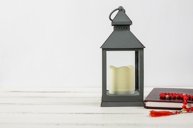 Candle in lantern holder; holy kuran book and red prayer beads on wooden desk against white backdrop Premium Photo