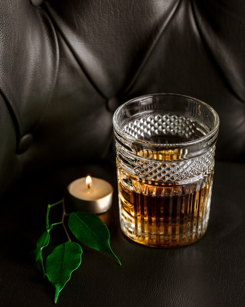 A candle, leaves and glass of whiskey Free Photo