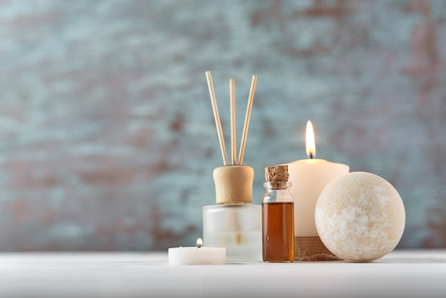 Candle and massage oil on white table Premium Photo