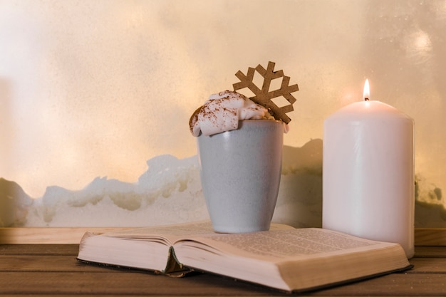 Candle near book and cup with toy snowflake on wood board near heap of snow through window Free Photo
