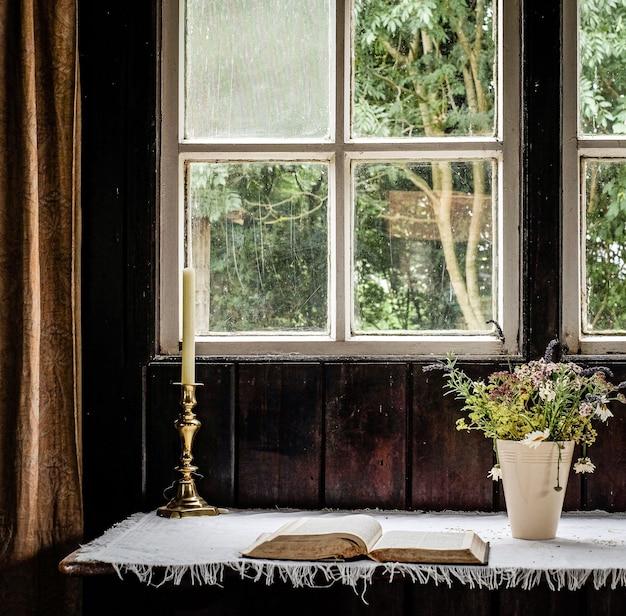 꽃 옆에 촛불을 놓고 창 앞에 책을 무료 사진