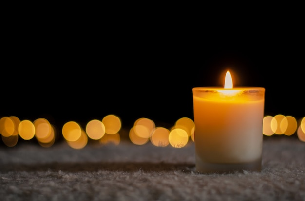 Свеча с огнями боке на рождество и новый год концепции. Premium Фотографии