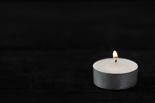 Candle with burning fire on black Premium Photo