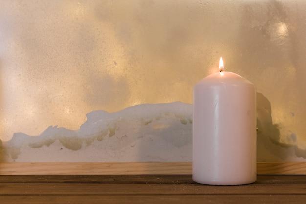 Candle on wood board near heap of snow through window Free Photo