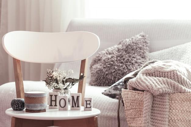 キャンドル、白い木製の椅子に家の木製の文字が付いている花が付いているつぼ。バックグラウンドにクッションが付いたソファと籐のバスケット。 無料写真