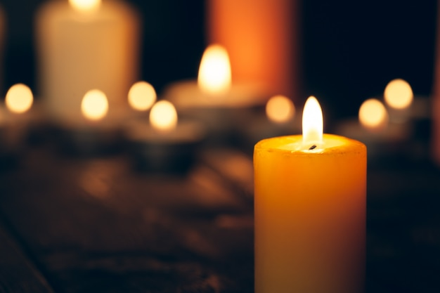 Candles burning in darkness over black. commemoration concept. Premium Photo