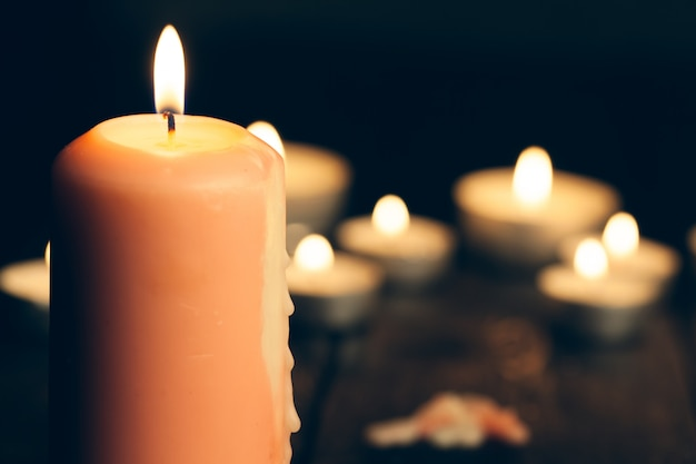 Candles burning in darkness over black. Premium Photo